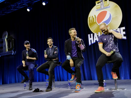 Jonny Buckland, left to right, Guy Berryman, Chris Martin and Will Champion of Coldplay answer questions during a halftime news conference for the upcoming NFL Super Bowl 50 football game Thursday, Feb. 4, 2016, in San Francisco.(AP Photo/David J. Phillip)
