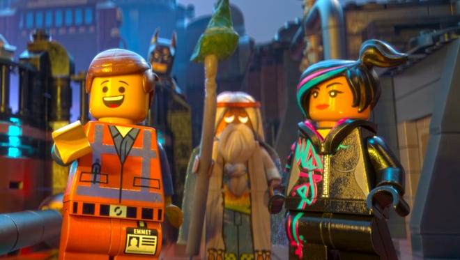 """A scene from the animated film """"The Lego Movie.""""  From left: Emmet (voiced by Chris Pratt), Batman (voiced by Will Arnett), Vitruvius (voiced by Morgan Freeman) and Wyldstyle (voiced by Elizabeth Banks)."""