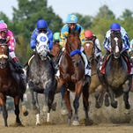 Triple Crown winner American Pharoah, cdenter, with jockey Victor Espinoza, leads the field into the first turn during the Travers Stakes horse race at Saratoga Race Course in Saratoga Springs, N.Y., Saturday, Aug. 29, 2015. (AP Photo/Hans Pennink)