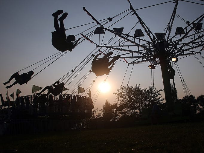 Visitors to the Middlesex County Fair ride the swings during the fourth day of the annual fair, Thursday, August 7, 2014, in East Brunswick, NJ. Photo by Jason Towlen