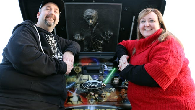 "Trey and Nancy Laymon of rural Oskaloosa are huge ""Star Wars"" fans who often drive around in a custom-decorated Ford Raptor pickup that has been signed by numerous stars of the films. Here the couple poses at the tail of the truck, which features a rubber mold of Han Solo encased in carbonite in the bed."