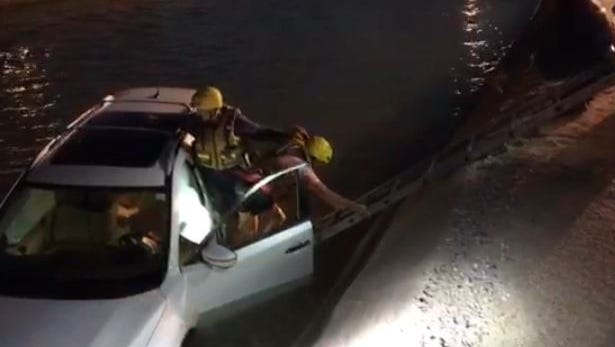 A Phoenix fire department technical rescue crew helps a woman from her partially submerged SUV after she drove into a canal in Paradise Valley on March 14, 2018.
