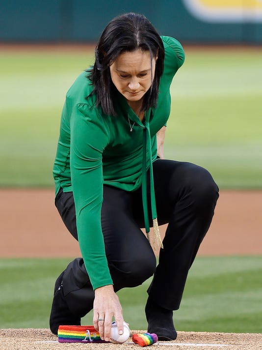 University of San Francisco women's basketball coach Jennifer Azzi places a baseball on the mound prior to a game between the Texas Rangers and the Oakland Athletics on Tuesday, June 14, 2016, in Oakland, Calif. Azzi, representing the LGBT community, took part in a ceremony replacing the traditional first pitch in memory of those who were slain in Orlando, Fla. (AP Photo/Ben Margot)