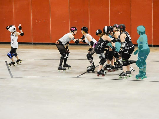 """Brittney """"Britt-knee Basher"""" Morris (far left,) calls off the jam, scoring five points for passing all five players on the opposing team. The other jammer (center with helmet star) scores points only for the highlighted players she has passed when the jam ends."""