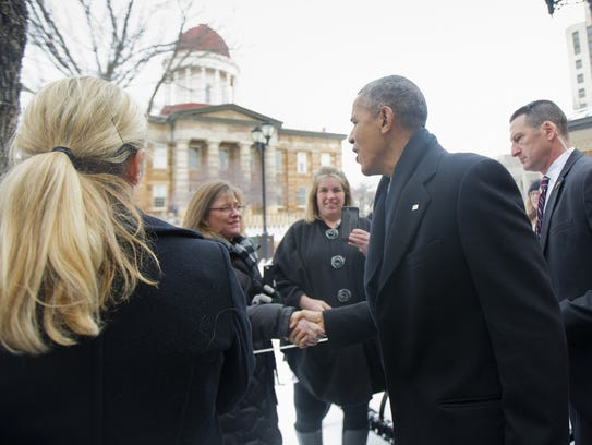 President Obama stops to greet people across from the