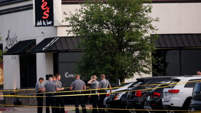 Police officers stand at the scene of a shooting on the east side of Lake Hefner in Oklahoma City, Thursday, May 24, 2018. A man armed with a pistol walked into Louie's On The Lake restaurant at the dinner hour and opened fire, wounding two customers, before being shot dead by a handgun-carrying civilian in the parking lot, police said.