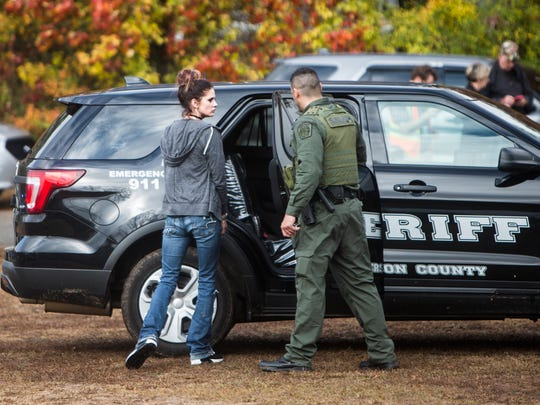An officer leads a handcuffed suspect into a police vehicle Tuesday at the scene of an officer-related shooting near Sexton Gin Road in Iva.