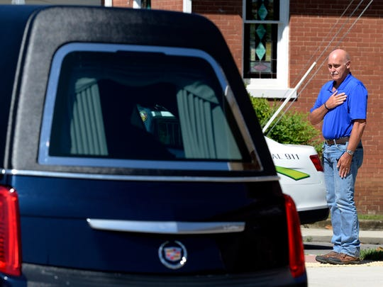 A resident watches as a motorcade passes by carrying the casket of Dickson County Sheriff Deputy Daniel Baker on Monday, June 4, 2018, in Dickson, Tenn. Sgt. Baker, a Marine veteran, was shot in the line of duty last week.