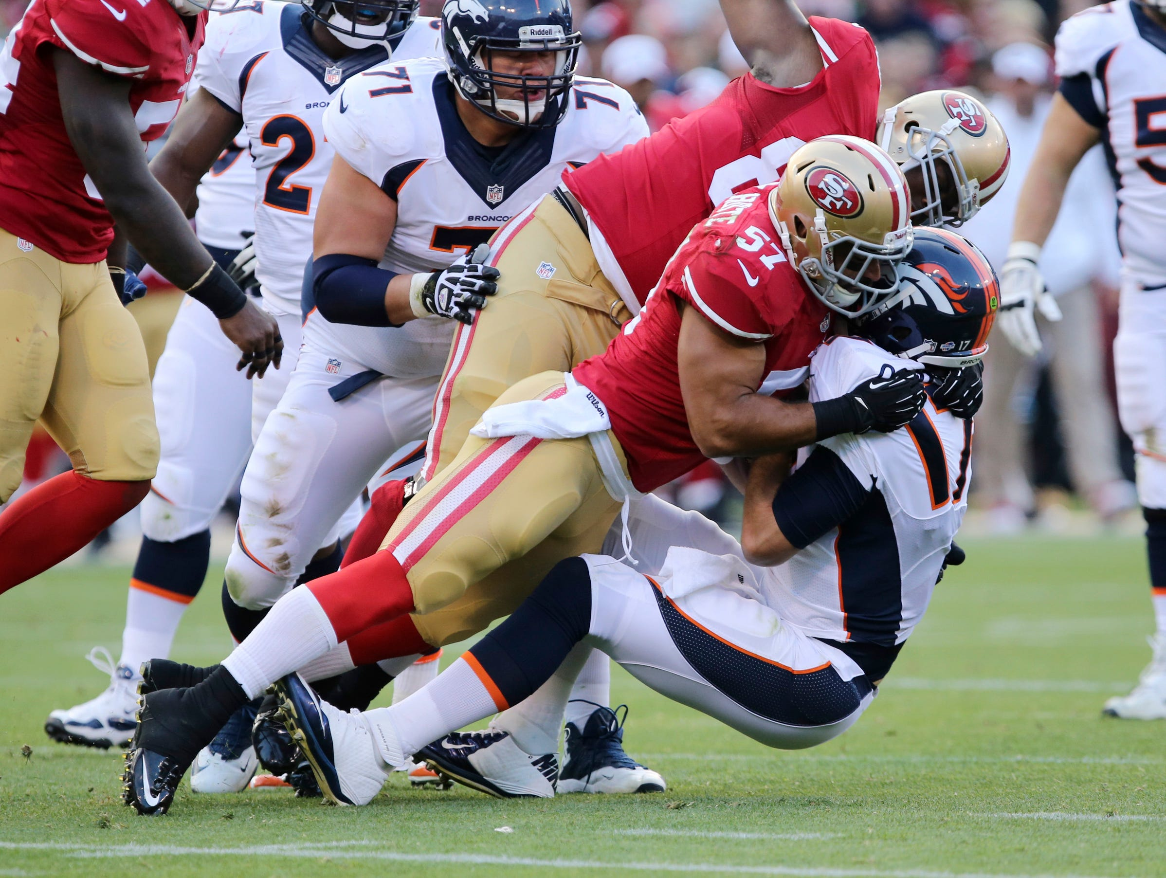 San Francisco 49ers linebacker Michael Wilhoite (57) and tight end Demarcus Dobbs (83) sack Denver Broncos quarterback Brock Osweiler (17) during the second quarter at Candlestick Park.