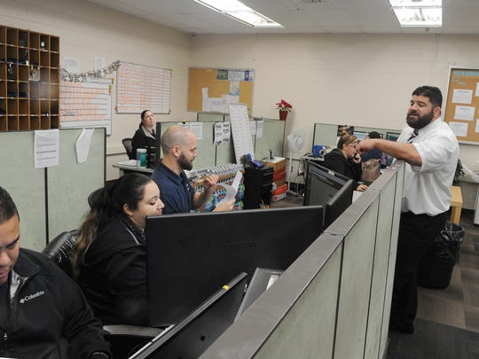 Chief Operating Officer Charles Sandlin right, of Roadrunner Shuttle and Limousine Service, talks with dispatchers Mario Saens, from left, Vilma Hernandez and Pete Foy.