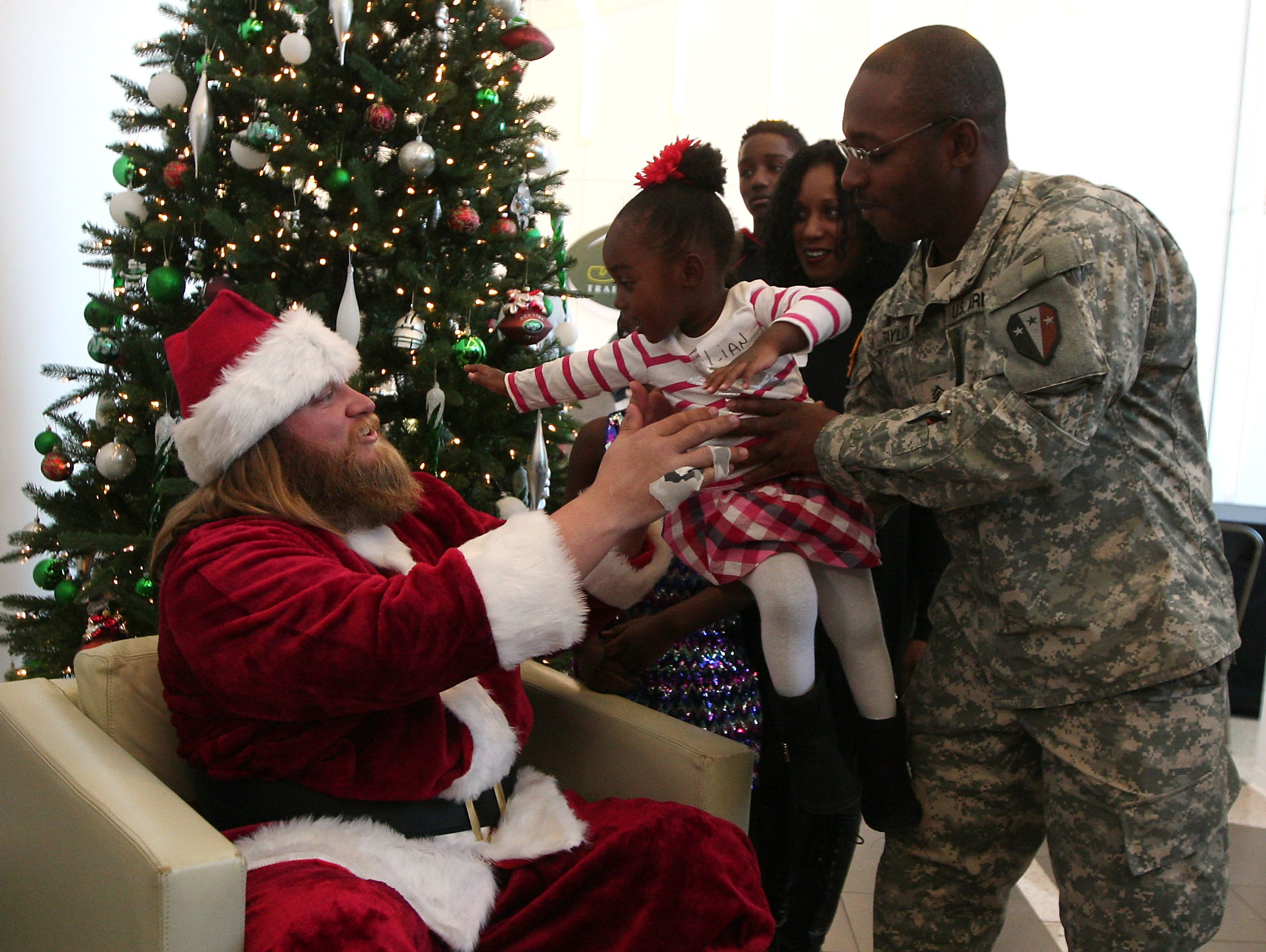 Donza Taylor of Bayonne hands over daughter 2-year-old Lian to Jets Pro Bowl center Nick Mangold as the New York Jets hosted a holiday party for military families at their Florham Park training facility. December 4, 2015, Florham Park, NJ.