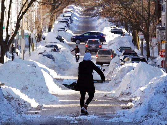Mollie Lane carries a shovel-full of snow down the