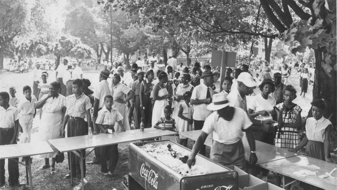 Crowds gather at the park for some picnicking activities.