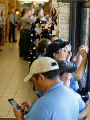 Employees of the Carlsbad Caverns gift shop along with Park Rangers line up along the windows of the gift shop taking photos of President Barack Obama and the first family as they left Carlsbad Caverns National Park in 2016 after touring a portion of the caverns.