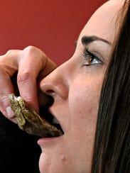 Lauren Atkins, of Manchester Township, eats a raw oyster