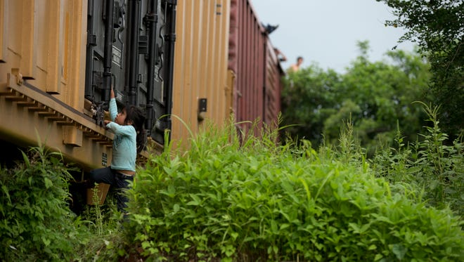In this Friday, June 20, 2014 photo, a young girl traveling with Central American migrants plays on the freight train they had been riding, after it suffered a minor derailment in a remote wooded area outside Reforma de Pineda, Chiapas state, Mexico. The number of unaccompanied minors detained on the U.S. border has more than tripled since 2011.