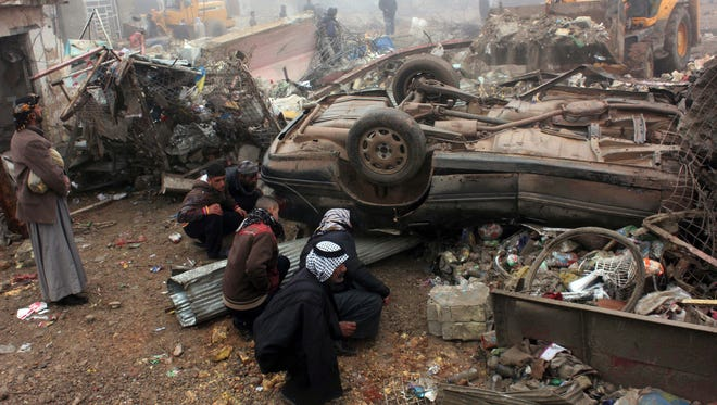 Civilians inspect the aftermath of a massive bomb attack in Balad Ruz, 45 miles northeast of Baghdad, on Friday.