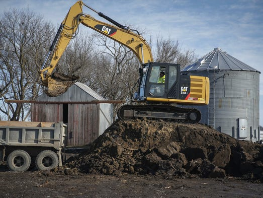 Crews continue to clean up the grounds of a farm in