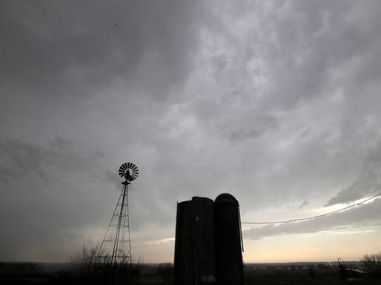 Thunderstorms pass over silos and a windmill near Baldwin