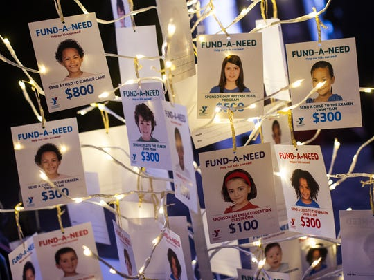 Photographs of children supporting different YMCA programs hang on a tree during the YMCA's Gold Garden Gala at the Naples Botanical Garden in Naples, Fla., on Saturday, Feb. 18, 2017. The Gold Garden featured special guests, including Naples resident, and YMCA member Michelle Konkoly, who won multiple gold medals at the 2016 Paralympic Games in Rio de Janeiro, along with Dr. James Naismith Jr., the grandson of the inventor of basketball.
