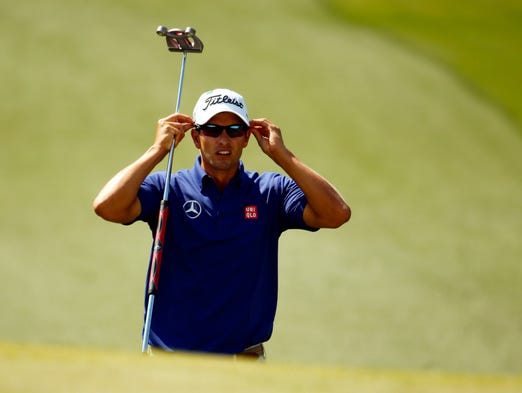 Adam Scott adjusts his sunglasses as he walks to the 7th green.