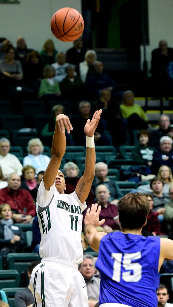 Binghamton University's Romello Walker hits a three-pointer while being covered by Hartwick's Joe Krong during a men's basketball game at the Events Center on Wednesday.