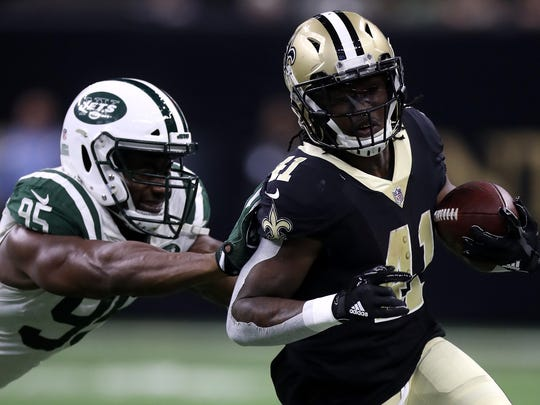 NEW ORLEANS, LA - DECEMBER 17:  Alvin Kamara #41 of the New Orleans Saints runs with the ball as  Josh Martin #95 of the New York Jets defends during the first half of a game at the Mercedes-Benz Superdome on December 17, 2017 in New Orleans, Louisiana.  (Photo by Chris Graythen/Getty Images)