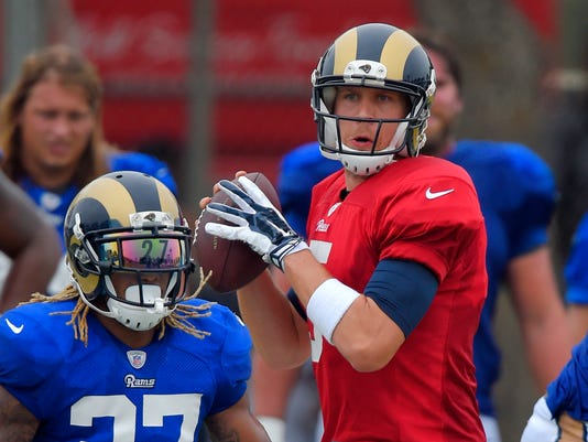 St. Louis Rams quarterback Nick Foles, right, passes as running back Tre Mason runs a play during a joint NFL football training camp with the Dallas Cowboys, Monday, Aug. 17, 2015, in Oxnard, Calif. (AP Photo/Mark J. Terrill)
