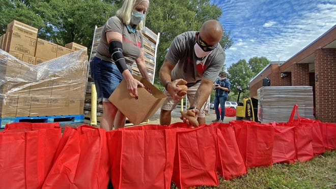 From left, Jenner Wall and John Beighan of Second Harvest Food Bank fill bags with sweet potatoes at Graham Elementary School on Wednesday.