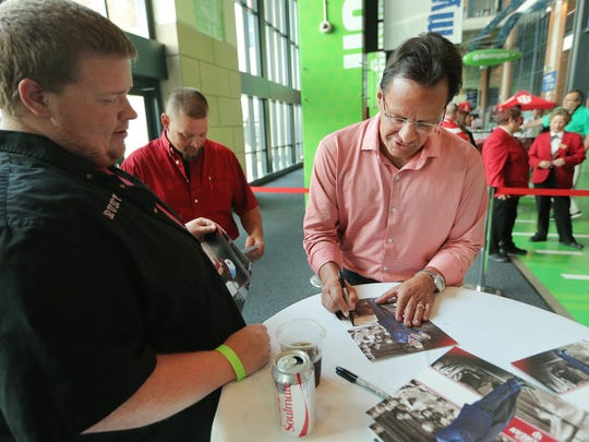 "Tom Crean signs autographs for Rusty Shields, left, and Bud Freeman, both of Bloomington, during the IU Booster ""On The Road"" event held at Lucas Oil Stadium on Aug. 27, 2015."