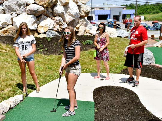 From left, twins Emily and Allison Lemmons, 14; Sam Ingram and Lemmons'  father, Chris, all of Dover Township, watch Allison's ball roll down the green at Mountain Mist Mini Golf in Dover Township.