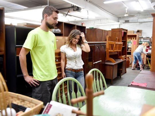 Re-Source York manager Enver Bilajac and Sheryl Kline of York Township inspect some of the wooden furniture for sale at the York store. Since Dec. 2015, Kline has purchased pre-owned wooden furniture pieces from stores such as Re-source York, restored and refurnished them and sold them to clients.