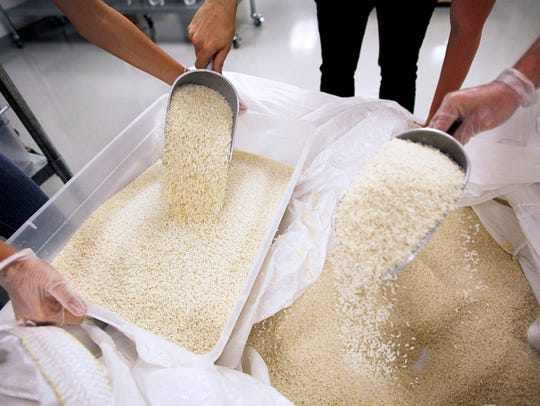 Rice is poured into a bin to be measured and portioned
