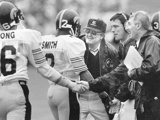 Iowa coach Hayden Fry, wearing hat, and assistant coach Kirk Ferentz (to Fry's left) celebrate a touchdown in the 1980s.