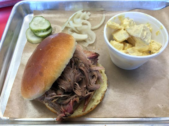 A pulled pork sandwich with side of potato salad at Naked BBQ in Phoenix.