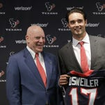Texans quarterback Brock Osweiler, right, holds his new jersey as he poses with owner Bob McNair during a news conference Thursday in Houston.
