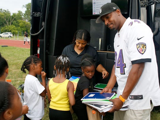 Crystal Washington, middle back, and Brandon Jackson, right, hand out school supplies after Camp Greatness on Wednesday, July 26, 2017 in Detroit.