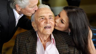 Actor Kirk Douglas, center, gets a kiss from his son Michael Douglas, left, and Michael's wife Catherine Zeta-Jones during his 100th birthday party at the Beverly Hills Hotel on Friday.