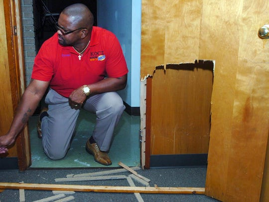 Opelousas Councilman Tyrone Glover inspects the damage to an office door at Little Zion Baptist Church where a break-in occurred late Monday night.