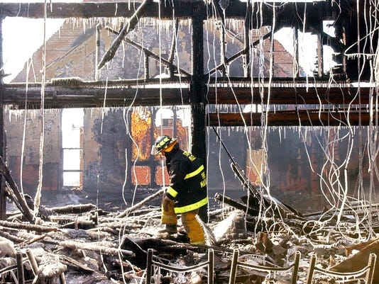 A Pa. State Police Fire Marshall is framed by the icy remains of Fawn United Methodist Church while he and other officials investigated the four-alarm fire in Fawn Grove on Thursday, March 3, 2005.