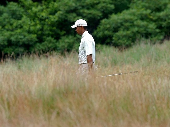 FILE - In this June 19, 2004, file phoo, Tiger Woods walks through the fescue to the sixth green during the third round of the U.S. Open golf tournament at Shinnecock Hills Golf Club in Southampton, N.Y. Woods will be playing the U.S. Open for the first time since 2015 at Shinnecock Hills on June 14-17, 2018. (AP Photo/Charles Krupa, File)