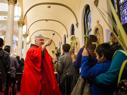 Pastor Todd Carpenter blesses worshippers and their palm leaves during Palm Sunday services at St. Paul's Catholic Church in Wilmington on Sunday morning.