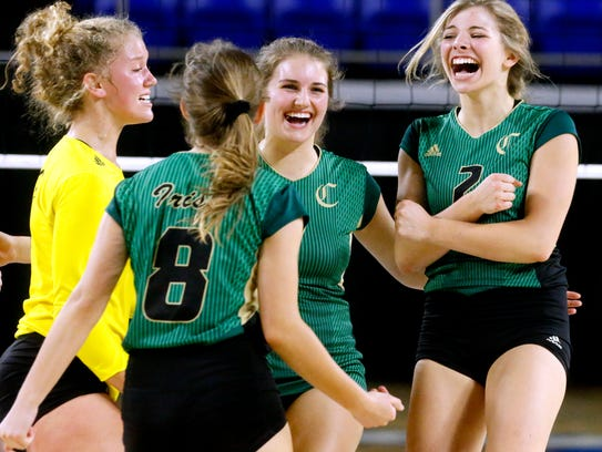 Knoxville Catholic players celebrate a point during the Class AA state championship volleyball game against Portland on Oct. 19 at MTSU.