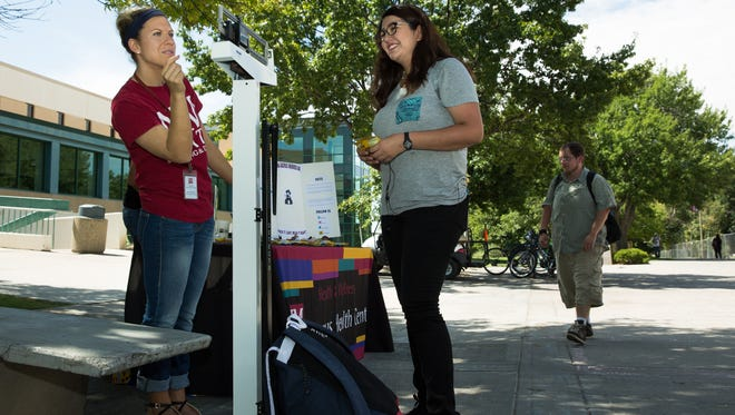Health Education Specialist for NMSU's Campus Health Center Kirsta Bezenek, left, weighs Berenice Rivera's backpack to be fifteen pounds during national backpack awareness day on the NMSU campus. Bezenek suggests to students to load a backpack or purse with no more than ten to fifteen percent of their body weight.