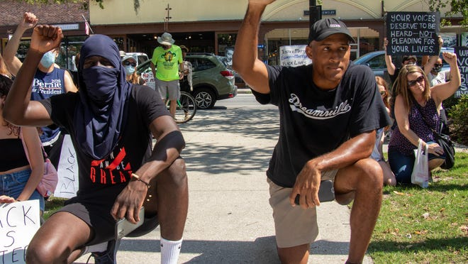 """Mouhamad Ba, left, and Rico Turner, right, participate in a May 31, 2020,  protest of the killing of unarmed African-American men at the hands of law enforcement at the Plaza de la Constitucion in downtown St. Augustine. Turner said protesting is about understanding, education and banding together to make an impact. """"Just because you see people of color and non people of color come together for these issues, know that it is done out of love and concern. We are here in peace, not violence."""""""
