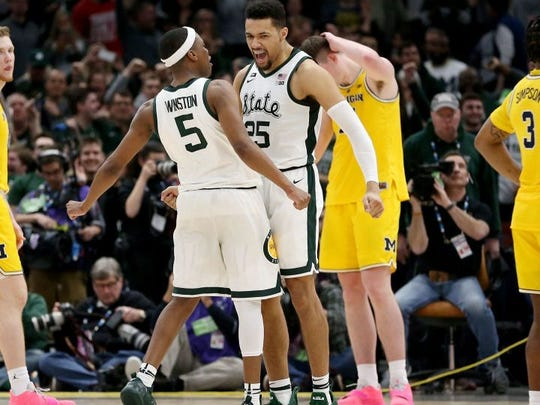 Cassius Winston, left, and Kenny Goins celebrate in the second half against Michigan on Sunday in Chicago.