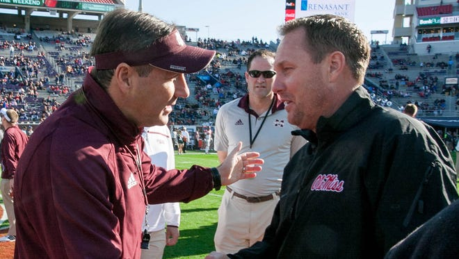 Mississippi State head coach Dan Mullen, left, and Ole Miss head coach Hugh Freeze meet at midfield prior to the 2016 Egg Bowl.