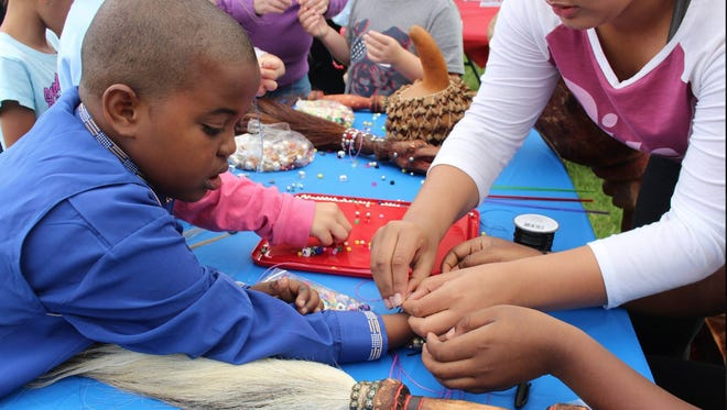 Children make bracelets at the 2017 Fred Yiran African Arts Day event.