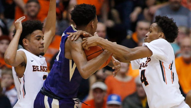 Washington's Dejounte Murray, center, is guarded by Oregon State's Stephen Thompson Jr., left, and Derrick Bruce during the first half of an NCAA college basketball game in Corvallis, Ore., Wednesday, Feb. 24, 2016.