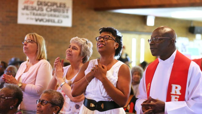 Pastor Curnell Graham, far right, and his wife Amy, during praise at the Gaines United Methodist Church. At left, is Mia Rhodenbaugh and Sue Peace, who are members at Armstrong Chapel, but were visiting on Graham's final service. He is transferring to a church in Columbus. The church is less than a mile from the shooting scene where Cincinnati Police Officer Sonny Kim lost his life in a shoot-out with Trepierre Hummons. Hummons also died.
